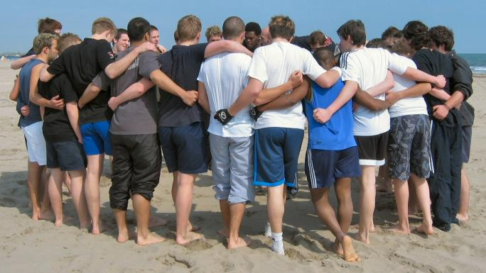 St Edmunds College in a training session huddle on Chioggia beach, Veneto.