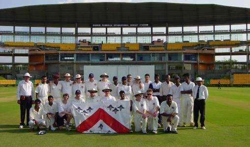 The Oundle School cricket team, from Northamptonshire, pose on the pitch.