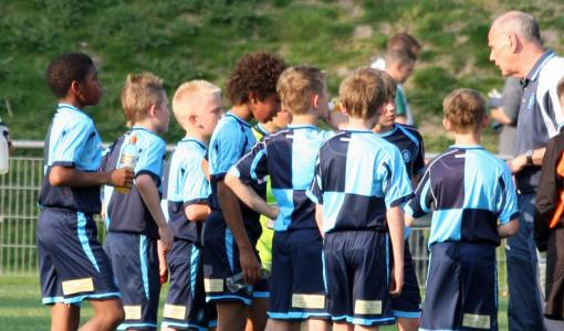 Footballers gather round the coach during practice