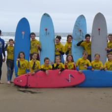 Students with surf boards on the beach, Northern Ireland.
